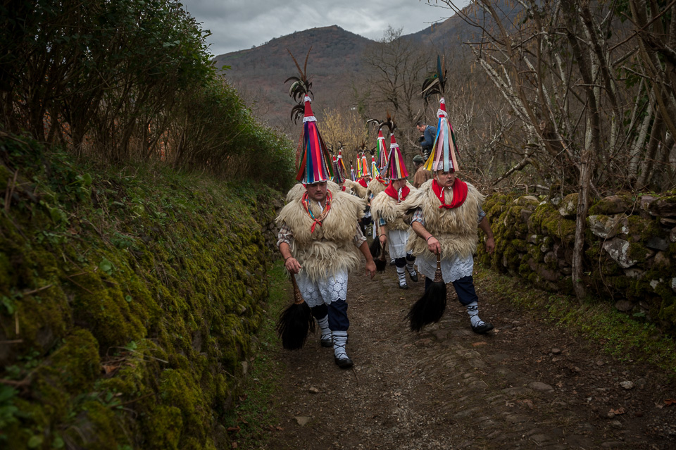 "Bellringers, walk on a country path. Ituren (Basque Country). January 30, 2017. The ""Joaldunak"" (""those who play the bell"") is a character that takes part in the carnival at the villages of Ituren and Zubieta carrying sheepskin and big cowbells tied to their backs, looking for a good new year, a good harvest and to keep away the bad spirits. (Gari Garaialde / BostokPhoto)"