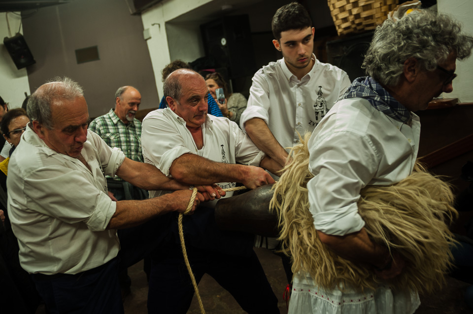 "Some people tie the cowbells of a bellringer during the celebration of an ancient traditional carnival. Zubieta (Basque Country). January 31, 2017. The ""Joaldunak"" (""those who play the bell"") is a character that takes part in the carnival at the villages of Ituren and Zubieta carrying sheepskin and big cowbells tied to their backs, looking for a good new year, a good harvest and to keep away the bad spirits. (Gari Garaialde / BostokPhoto)"